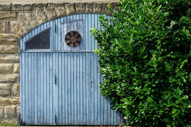 Grande portão de madeira velho com um ventilador em uma parede de pedra e um grande arbusto verde