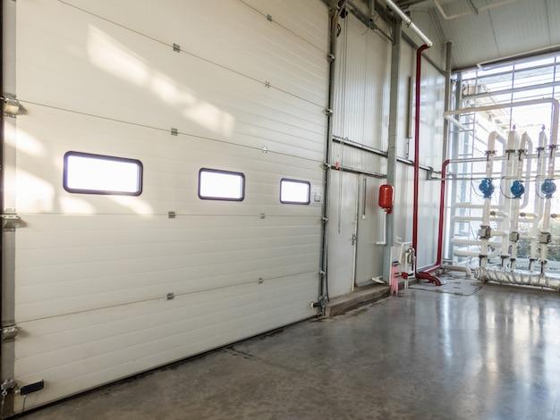 Grande portão fechado com janelas na fábrica. tubos e motor
