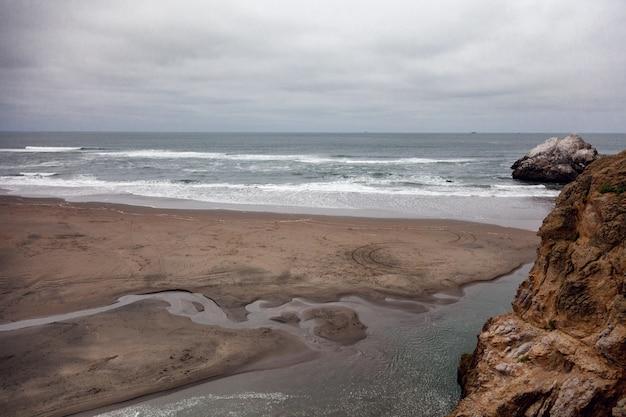 Grande praia deserta, bela vista do oceano, grandes pedras
