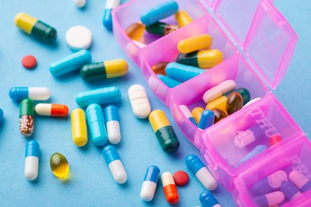 Grande quantidade de comprimidos em fundo azul com um organizador de caixa ou lembrete para tomar comprimidos