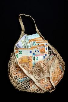 Grande quantidade de dinheiro em euros em uma rede de algodão reutilizável