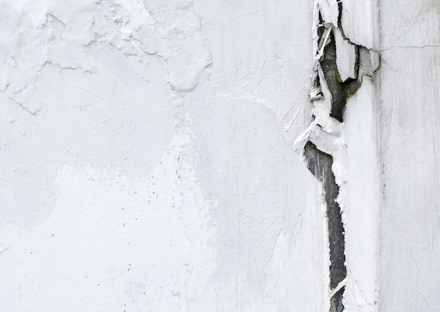 Grande rachadura no muro de cimento branco.