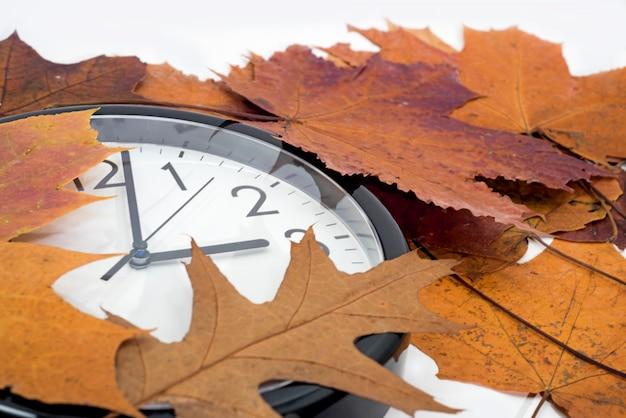 Grande relógio preto com folhas de outono.