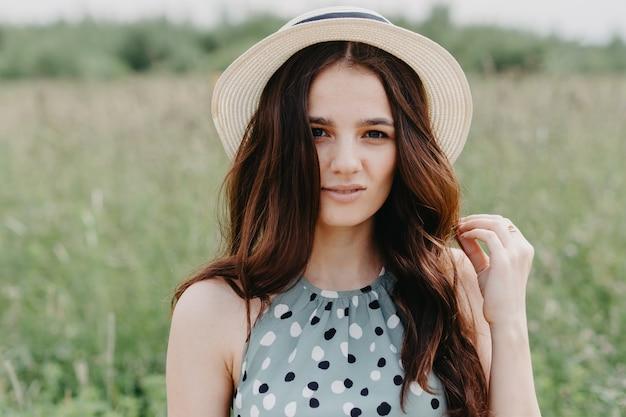 Grande retrato de uma jovem com um chapéu de palha em um campo verde de verão