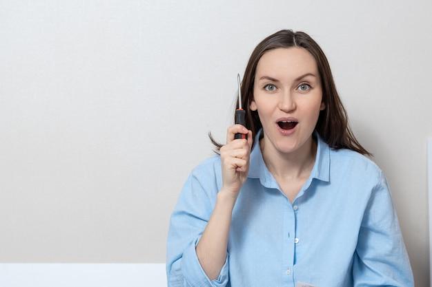 Grande retrato de uma jovem mulher com uma chave de fenda nas mãos dela