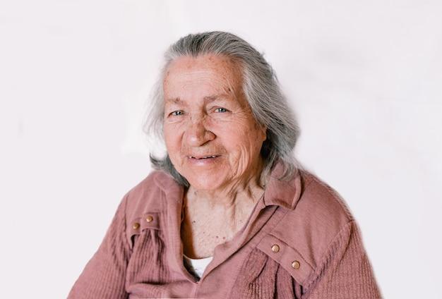 Grande retrato de uma mulher idosa em um fundo branco isolado, idosos aposentados