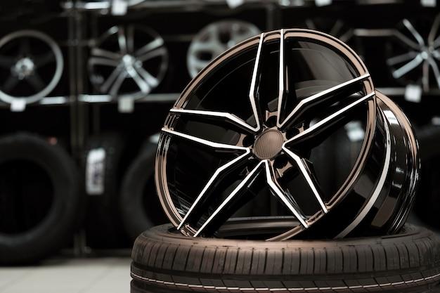 Grande roda leve de liga leve esportiva no fundo de uma loja de pneus, close-up.
