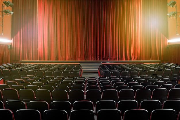 Grande sala de teatro iluminada com poltronas vazias