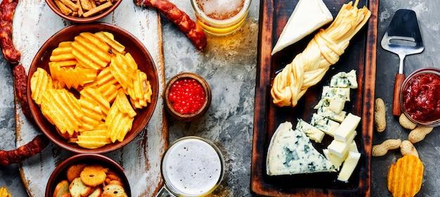 Grande seleção de lanches para cerveja. conjunto de queijos, peixe, batatas fritas e snacks