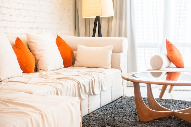 Grande sofá com almofadas e mesa de vidro