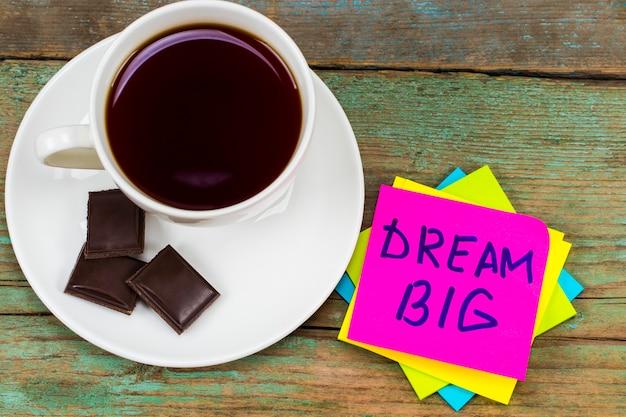 Grande sonho - caligrafia inspiradora em uma nota adesiva rosa com uma xícara de café e chocolate.
