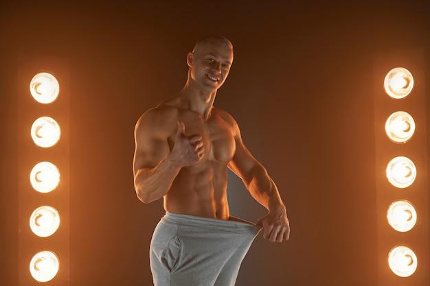Grande tamanho masculino. jovem cara musculoso puxando as calças e mostrando o polegar para cima gesto, orgulhoso e satisfeito com seus órgãos genitais, iluminação de lâmpadas no fundo conceito de perda de peso dieta
