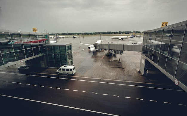 Grande terminal de aeroporto com aviões nos portões de embarque em dia chuvoso