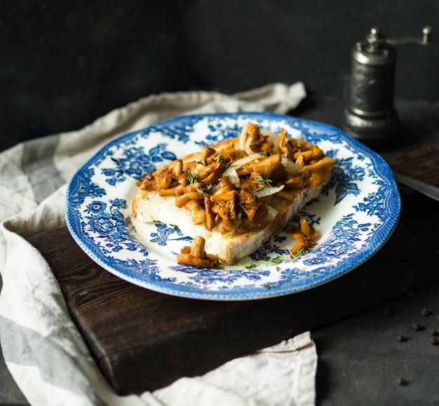 Grande torrada com chanterelles fritos onn antiga placa azul no escuro
