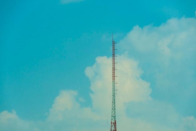 Grande torre vermelha e branca e o fundo do céu e das nuvens