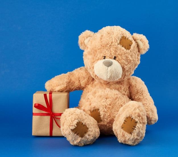 Grande ursinho bege segura uma caixa embrulhada em papel pardo e amarrada com uma fita vermelha