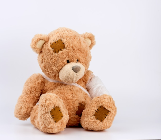 Grande urso de pelúcia bege com patches senta-se sobre um fundo branco, a pata esquerda é enfaixada com uma bandagem médica branca