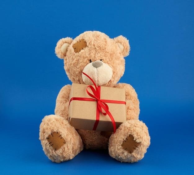 Grande urso de pelúcia bege segura uma caixa embrulhada em papel pardo