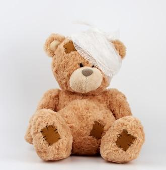 Grande urso de pelúcia com uma cabeça enfaixada em uma bandagem médica branca sobre um fundo branco
