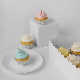 Grande variedade de cupcakes com caixas de embalagem e prato
