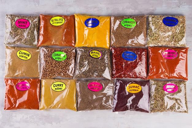 Grande variedade de especiarias embaladas em sacos os nomes das especiarias estão listados em turco