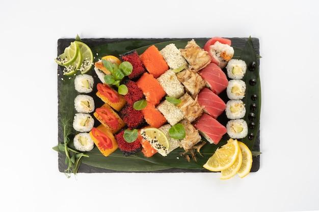 Grande variedade de maki de sushi variado feito de salmão, atum, ovas de camarão de peixe voador tobiko, arroz e sementes de gergelim em um planalto de pedra ardósia preta