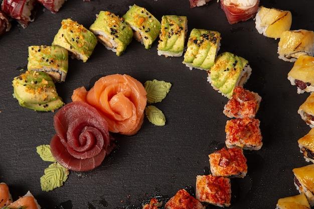 Grande variedade de rolos de sushi e fatias de salmão moldando rosas na superfície preta