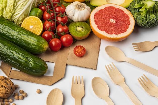 Grande variedade de vegetais com saco de papel e talheres de madeira