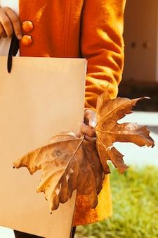 Grande venda de outono. mulher segurando uma folha de outono grande e sacola de compras. grande desconto de venda da temporada de outono