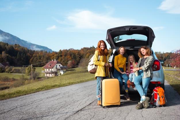 Grande viagem em família - meninas felizes viajam de carro. mamãe com filhas sentadas no porta-malas