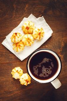 Grande xícara de chá com bolinhos minúsculos na mesa de madeira