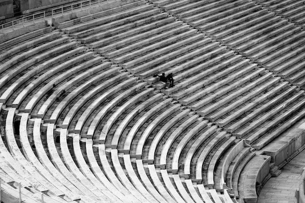 Grandes assentos do estádio com poucas pessoas