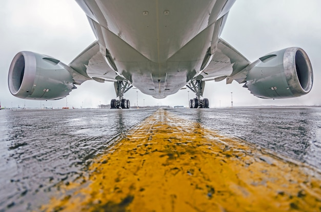 Grandes aviões de passageiros estacionados no aeroporto, vista inferior, chassi e motores.