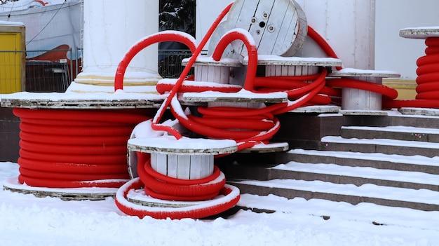 Grandes bobinas de tubo corrugado flexível vermelho usado para proteger cabos em instalações elétricas. muitas mangueiras de plástico de polietileno coloridas usadas na construção de sistemas de encanamento.