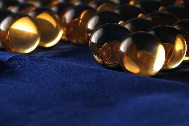 Grandes bolas de vidro transparente em close-up ficam lado a lado em um pano escuro.