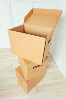Grandes caixas de papelão em pé insinde um quarto