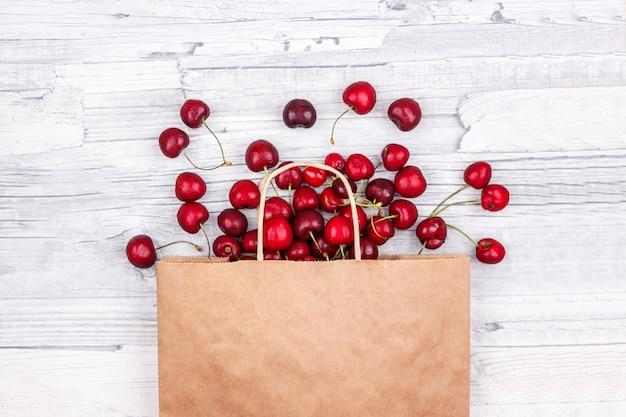 Grandes cerejas doces maduras em um saco de papel.