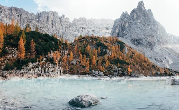 Grandes colinas e falésias. dia de outono nas montanhas majestosas. árvores de cor amarela nas rochas. belo lago de cristal