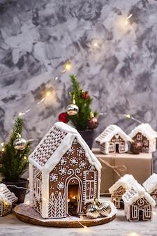 Grandes e pequenas casas de gengibre - uma aldeia de casas de gengibre sobre um fundo cinza com luzes