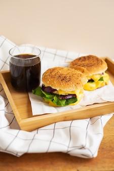 Grandes e saborosos hambúrgueres grelhados com sementes de gergelim repousam sobre uma bandeja de madeira com um copo de coca-cola. mesa de madeira e guardanapo xadrez branco.