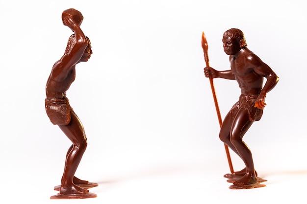 Grandes figuras de brinquedo de pessoas primitivas em um fundo branco