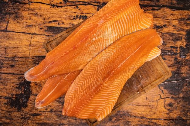 Grandes filés de salmão crus em uma tábua de madeira