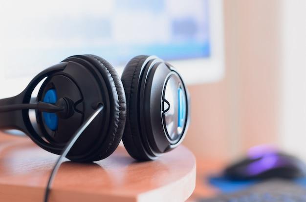 Grandes fones de ouvido pretos ficam na área de trabalho de madeira do som