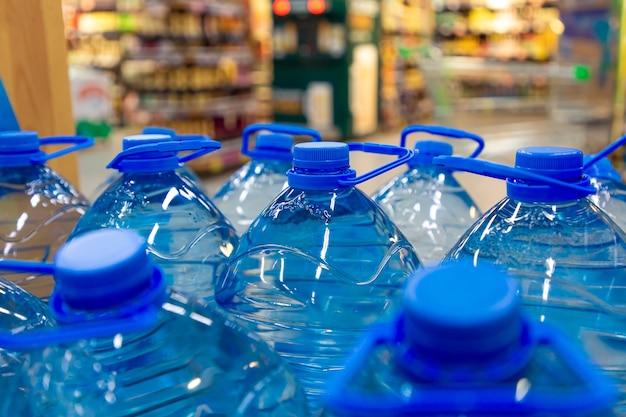 Grandes garrafas de 5 litros de água, detalhe da pilha de água engarrafada na loja.