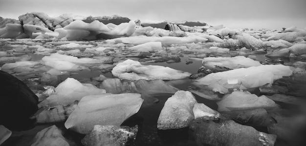 Grandes icebergs destacados da língua de uma geleira atingindo a costa