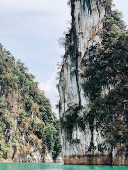 Grandes ilhas exóticas e tropicais verde-escuras com rochas e lago turquesa no lago cheow lan, khao phang, distrito de ban ta khun