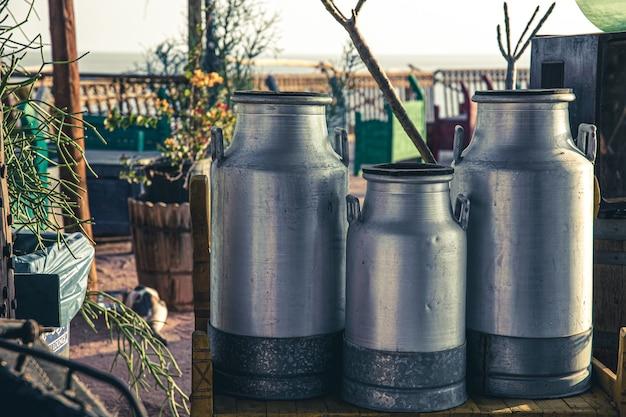 Grandes latas de leite velhas de metal no lindo pôr do sol