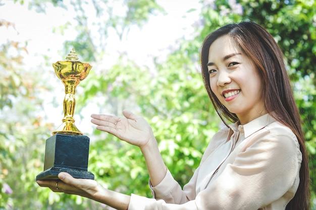 Grandes mulheres trabalhadoras alcançam seus objetivos com sucesso, recebendo troféus de ouro.