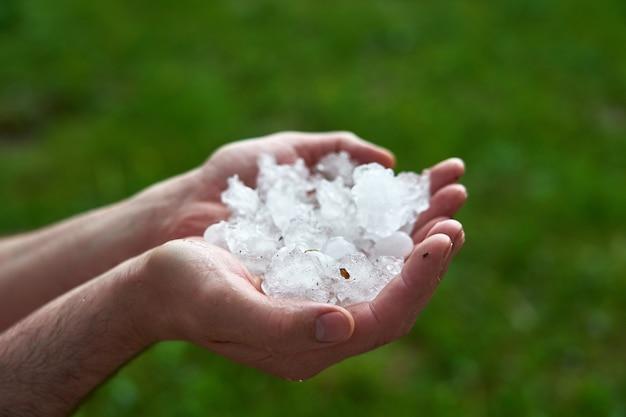 Grandes pedaços de gelo granizo na palma da sua mão. homem segurando um punhado de pedras de granizo grandes. consequências de anomalias naturais.