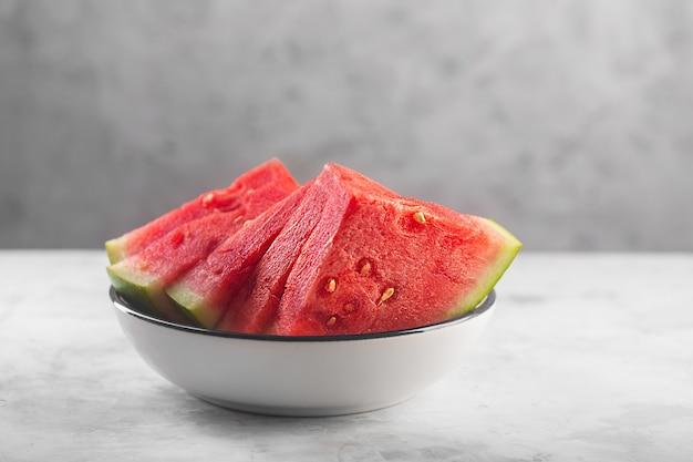 Grandes pedaços de melancia crua vermelha em fundo cinza